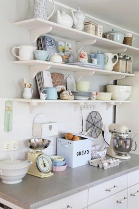 Nostalgic appliances on kitchen counter below vintage and retro crockery on bracket shelves