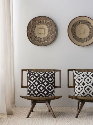 03_11-Dark-wood-chairs-upholstered-with-ethnic-woven-fabrics-and-matching-pottery-on-the-wall